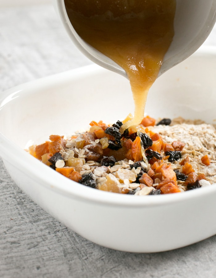 Vegan fruit flapjacks method: dried ingredients in a white casserole dish, wet ingredients in a small white cup slowly poured into the dry mixture