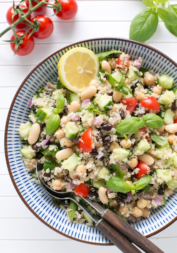 quinoa salad with tomatoes, beans, basil, and lemon on a serving bowl