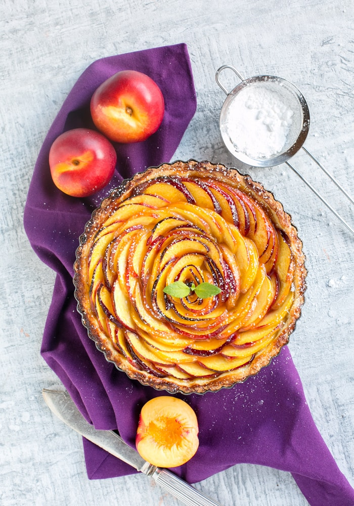 nectarine tart over a purple napkin, two nectarines on the top left, a sieve with powdered sugar on the top right side, half nectarine and a knife on the bottom,