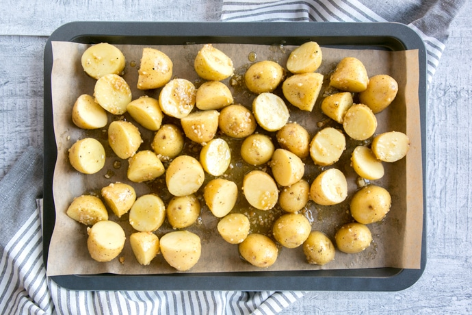 recipe step 1: new potatoes with olive oil and pesto on a baking sheet