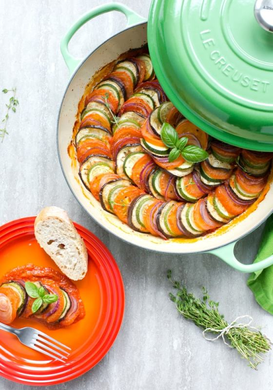 Easy Ratatouille in a large green cast iron shallow pan, bunch of thyme sprigs on the left side and a green napkin on the top right side. Red small dish with a slice of bread a small portion of ratatouille and fork on the left side of the image.
