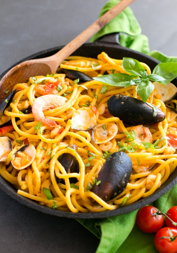 The easiest Seafood Fresh Pasta recipe, made with clams, mussels, squid and shrimp in a creamy and rich tomato sauce. A quick and delicious dinner that you can whip up in less than 20 mins! Recipe by The Petite Cook