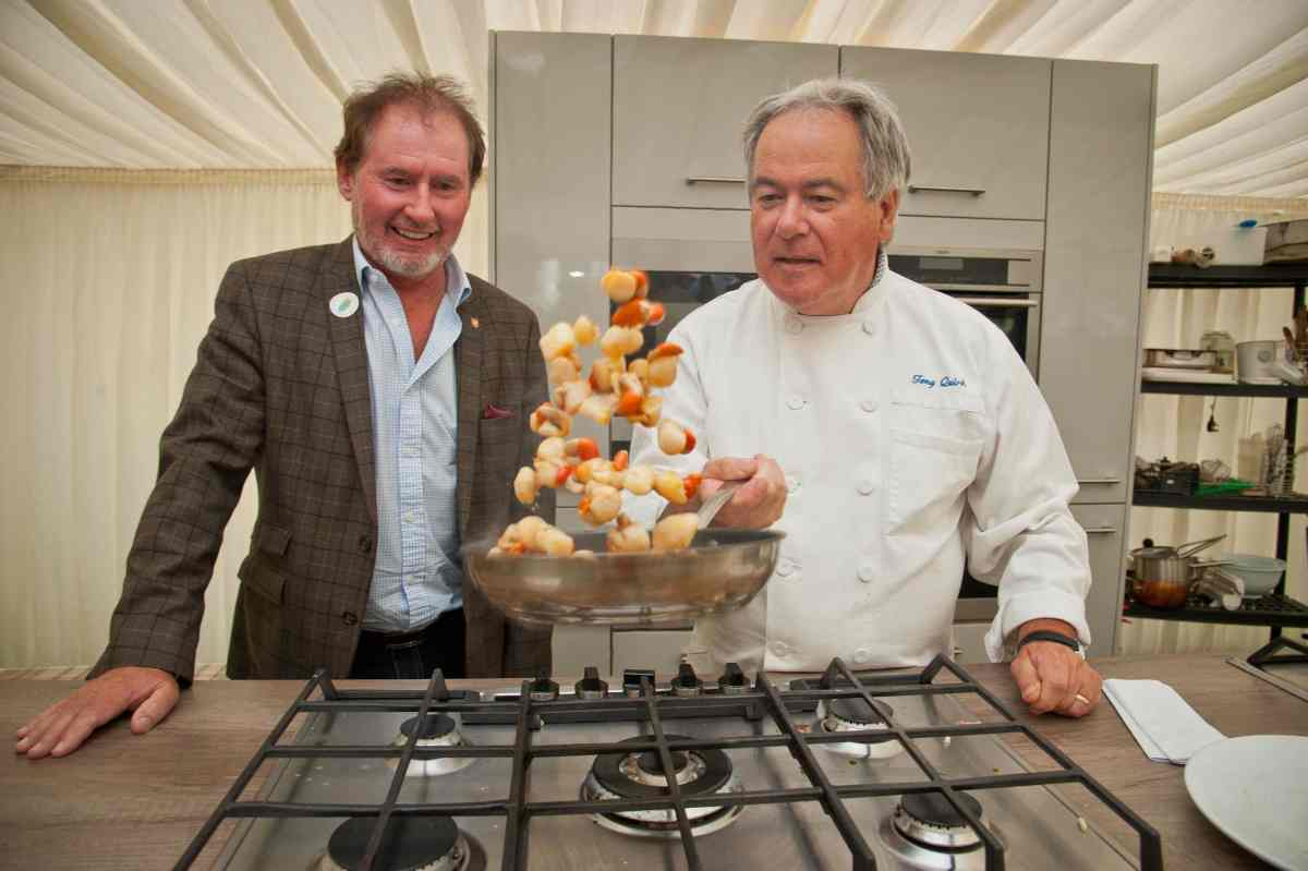 Chef Tony Quirk cooking queenies in a pan over the hobs, next to Hon Geoffrey Boot, Minister for Environment, Food and Agriculture.