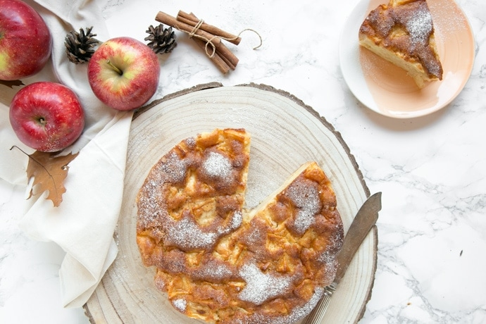 Italian apple cake on wood board next to apples, cinnamon sticks and a small plate with a slice of cake