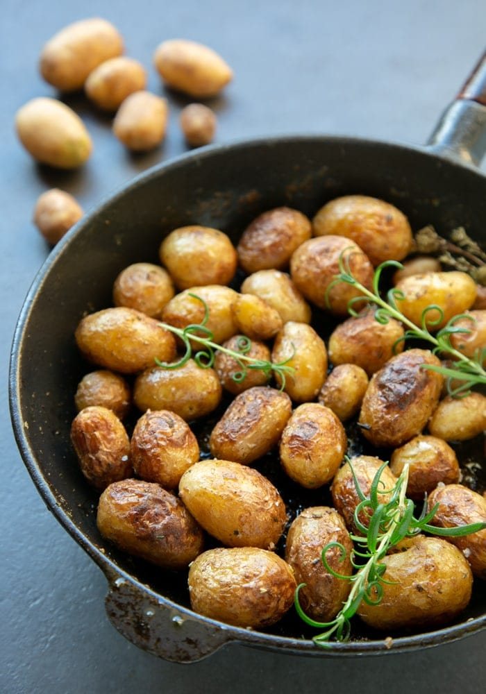 Italian pan roasted new potatoes with rosemary in skillet, raw potatoes in the background