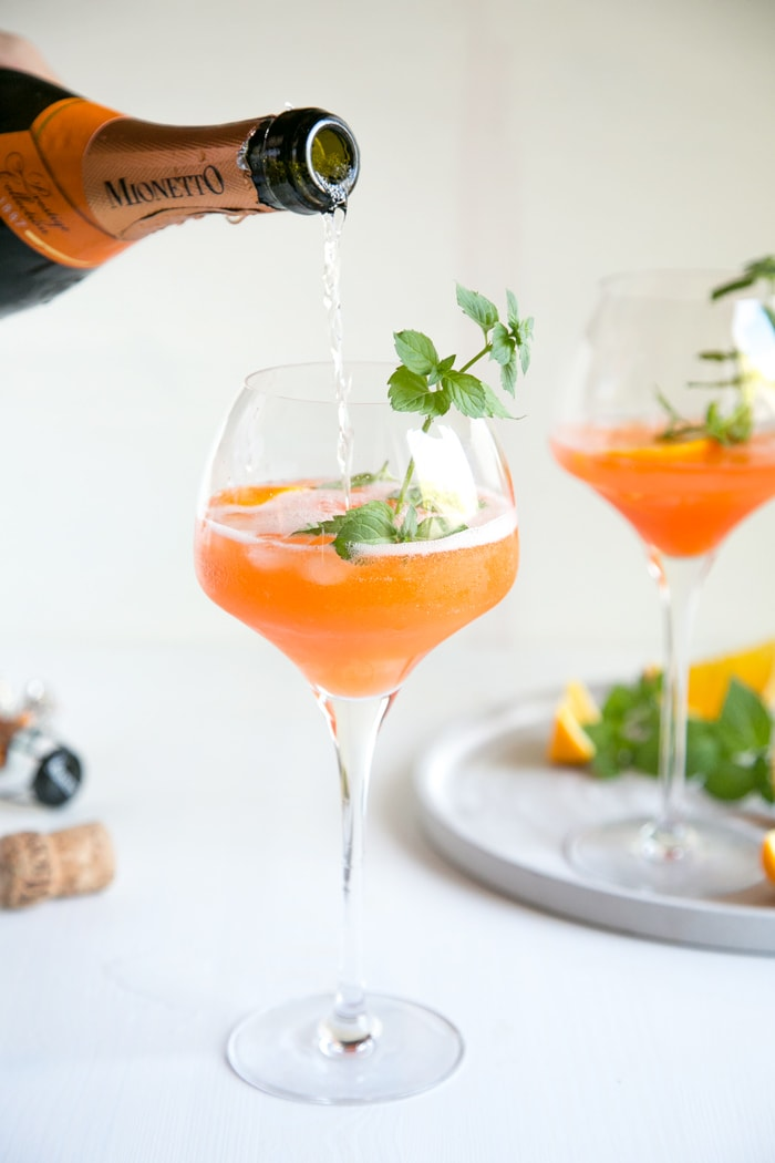 prosecco pouring from bottle into orange spritz glass garnished with mint leaves