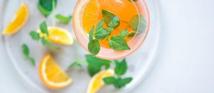 italian orange spritz in large wine glasse decorated with orange slice and fresh mint leaves