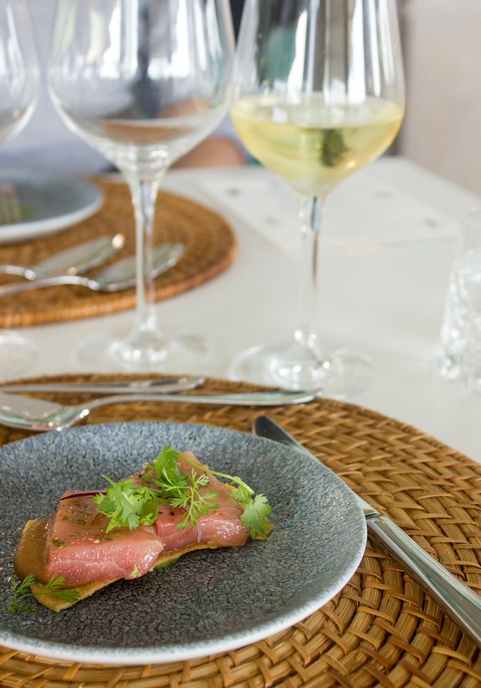 fresh tuna fillet on toast and charro black beansand guacamole, served on a blue plate with white wine on the side, table setting in the background