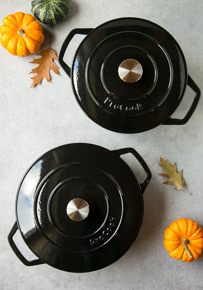 ProCook black cast iron casserole set, mini pumpkins and autumn leaves on the background