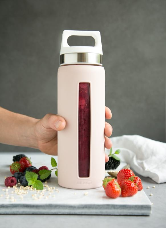 mixed berry smoothie in sigg bottle in pink, grabbed by a hand , berries and a white napkin to decorate in the background