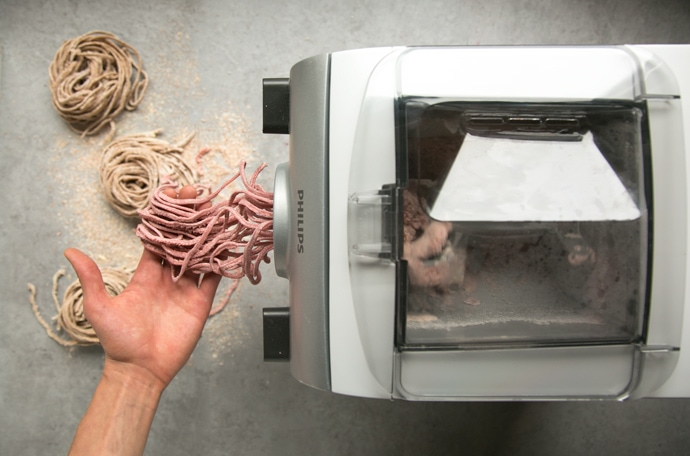 hand catching fresh tagliiolini out of the pasta machine, tagliolini nests on the background