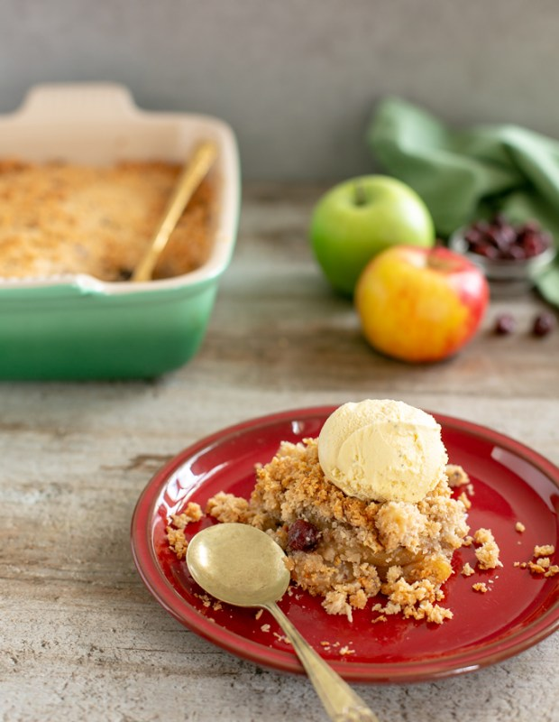 crumble in a red dish topped with vanilla ice cream next to gold spoon. Baking dish and 1 red apple and 1 green apple in the background.