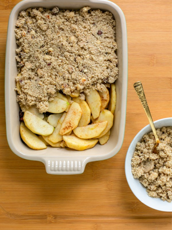 recipe step 2: baking dish with apple filling topped half-way through with the crumble topping, a small white plate filled with crumble topping and a spoon, next to the baking dish