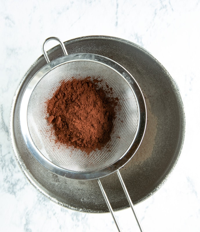 muffins recipe step 2: cocoa powder in sifter over metal bowl