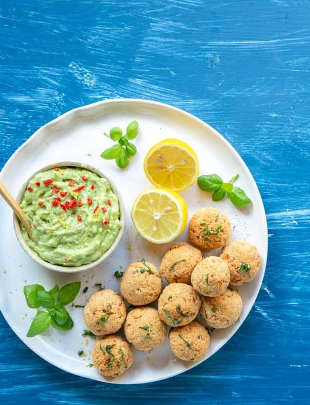 flat lay image of baked salmon meatballs on white plate served with halved lemon, basil leaves and avocado cream in a small pot