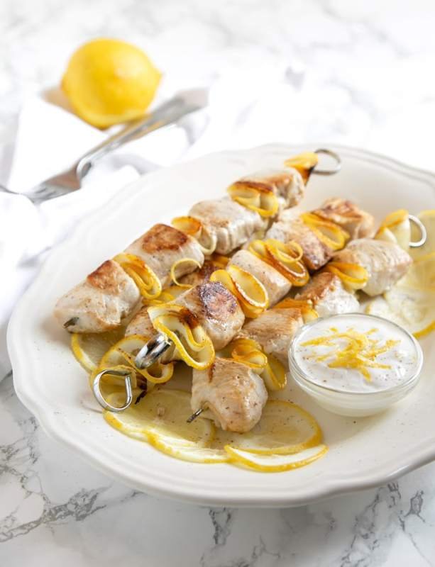 lemon chicken skewers and small pot with yogurt dip and lemon slices onto white serving plate. Lemon and for on a white napkin in the backgroun