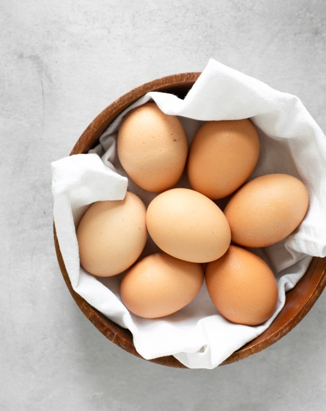 eggs in a wood bowl covered with a white napkin