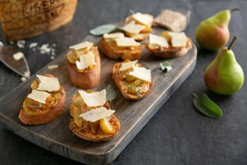 Bruschetta with Caramelised Pears & Grana Padano Riserva on a wood board, in the background wheel of grana padano cheese, cheese knife and two pears.