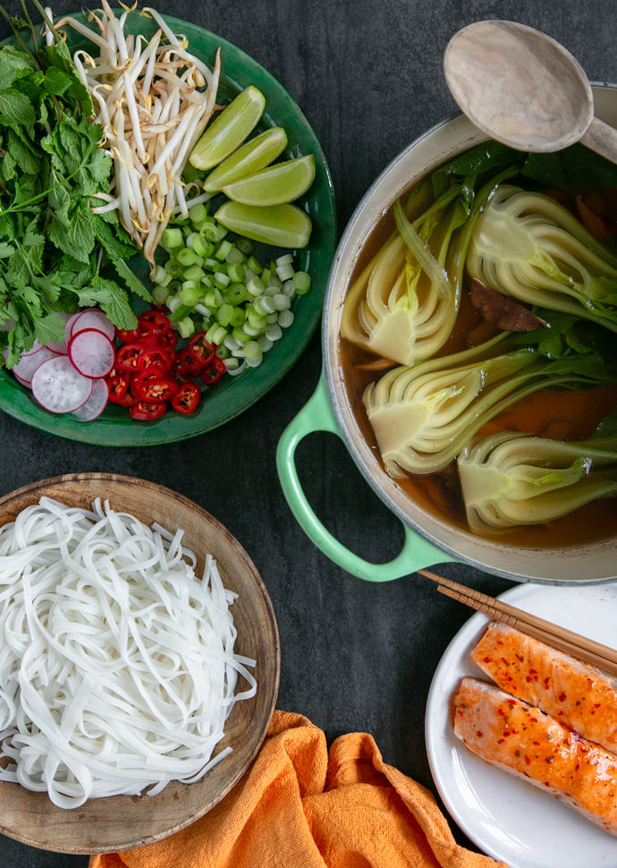 pho broth with shiitake and pak choi in a large pot, next to a plate with rice noodles, next to a plate with grilled salmon, next to a plate with pho toppings such as mint leaves, lime wedges, bean sprouts, sliced red chilli, sliced spring onion and red chilli
