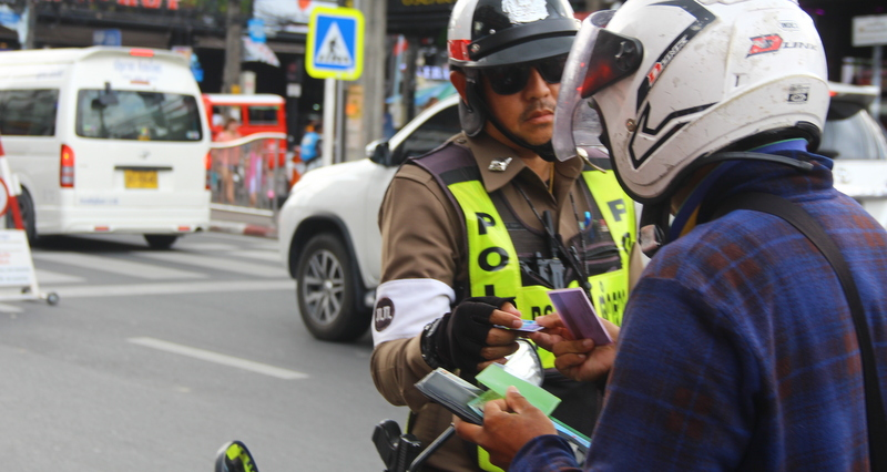 A police officer checks a motorcycle rider's driver's licence in Patong this week. Photo: Tanyaluk Sakoot