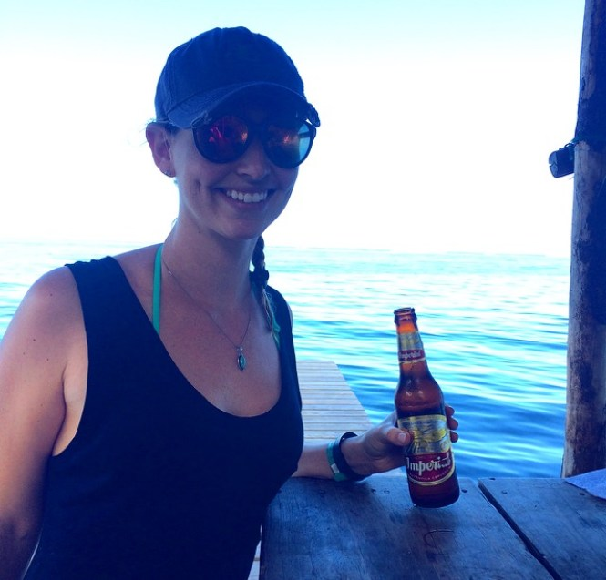 a female traveller enjoying the island life with a beer in Roatan, Honduras