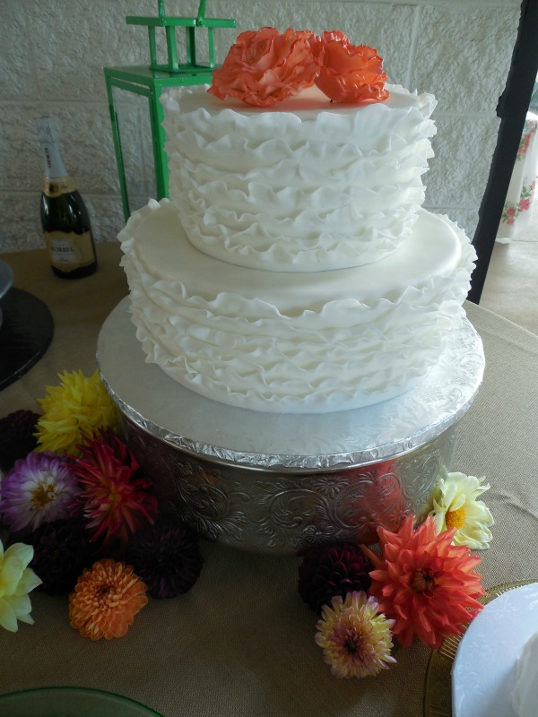 Wedding Cake Cost Considerations That Add Up    The Pink Bride white ruffled wedding cake with orange flowers  provided by tricities cake  bakery the cake gallery
