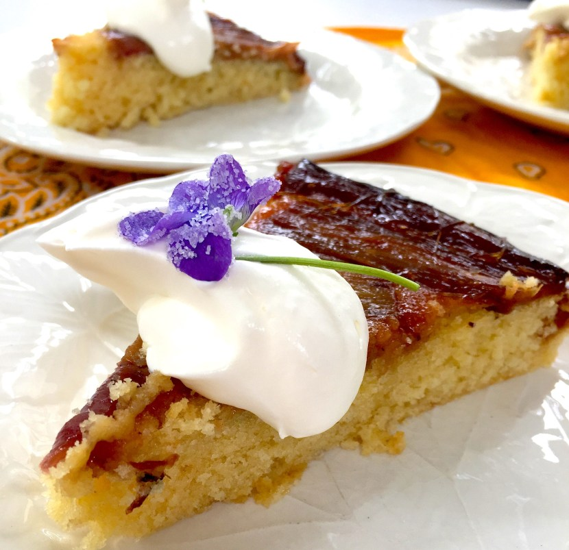 Rhubarb cake with whipped cream and candied Violets.