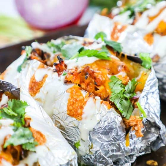 BBQ Chicken Baked Potato Recipe topped with cheese, sour cream and cilantro.