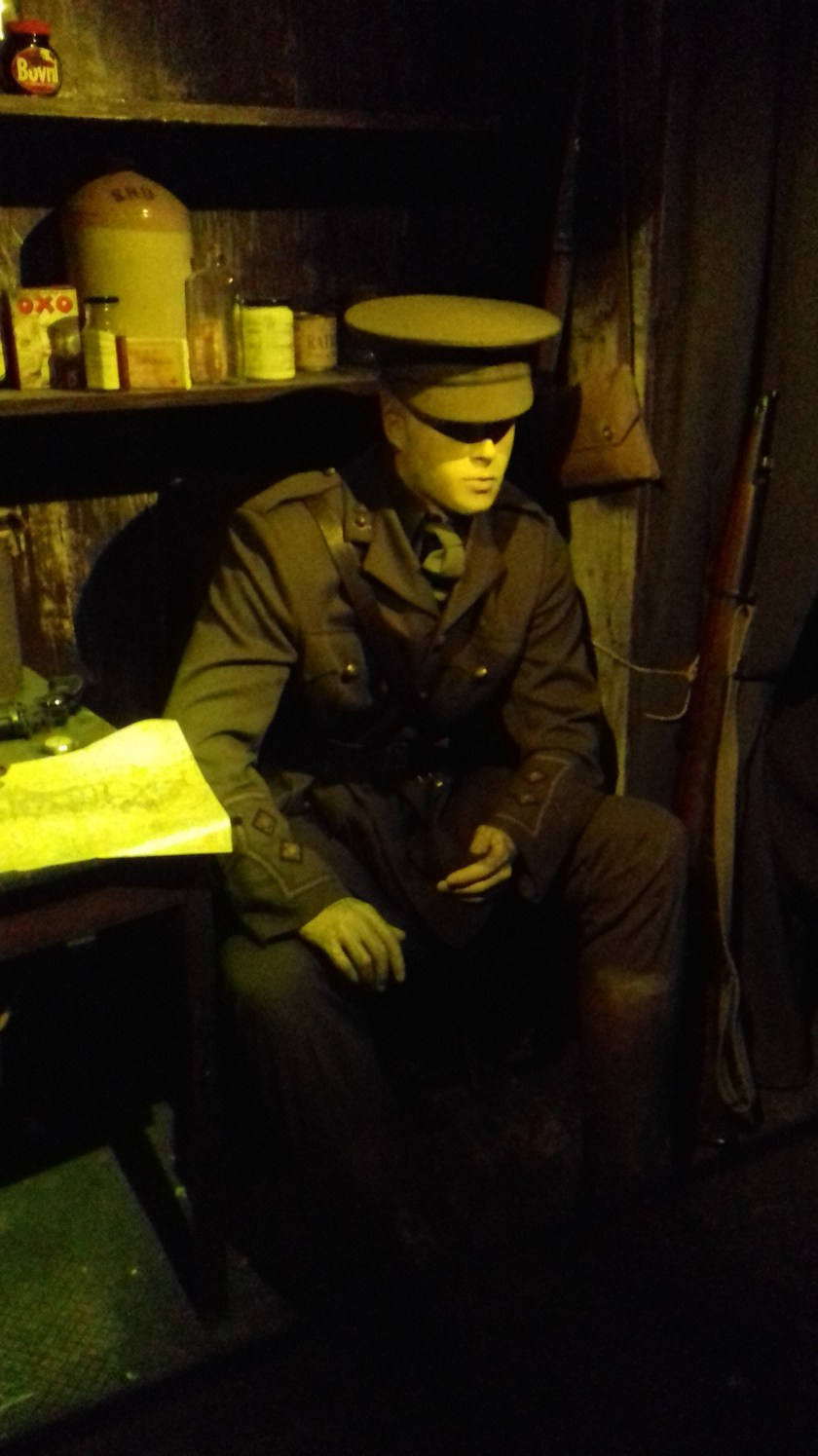 The photo shows a soldier sitting in a trench
