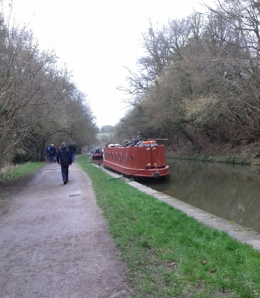 The canal tow path with a red narrow boat