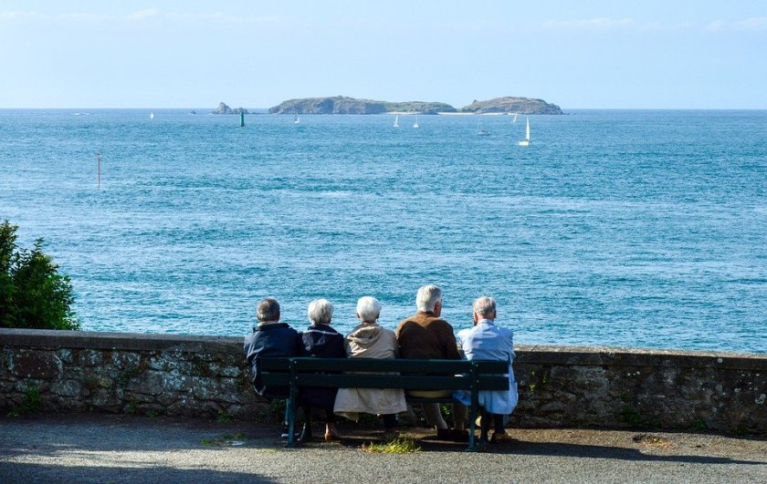 A group of old people sat on a bench looking out to sea.
