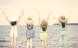 summer holidays and vacation – girls with hands up on the beach