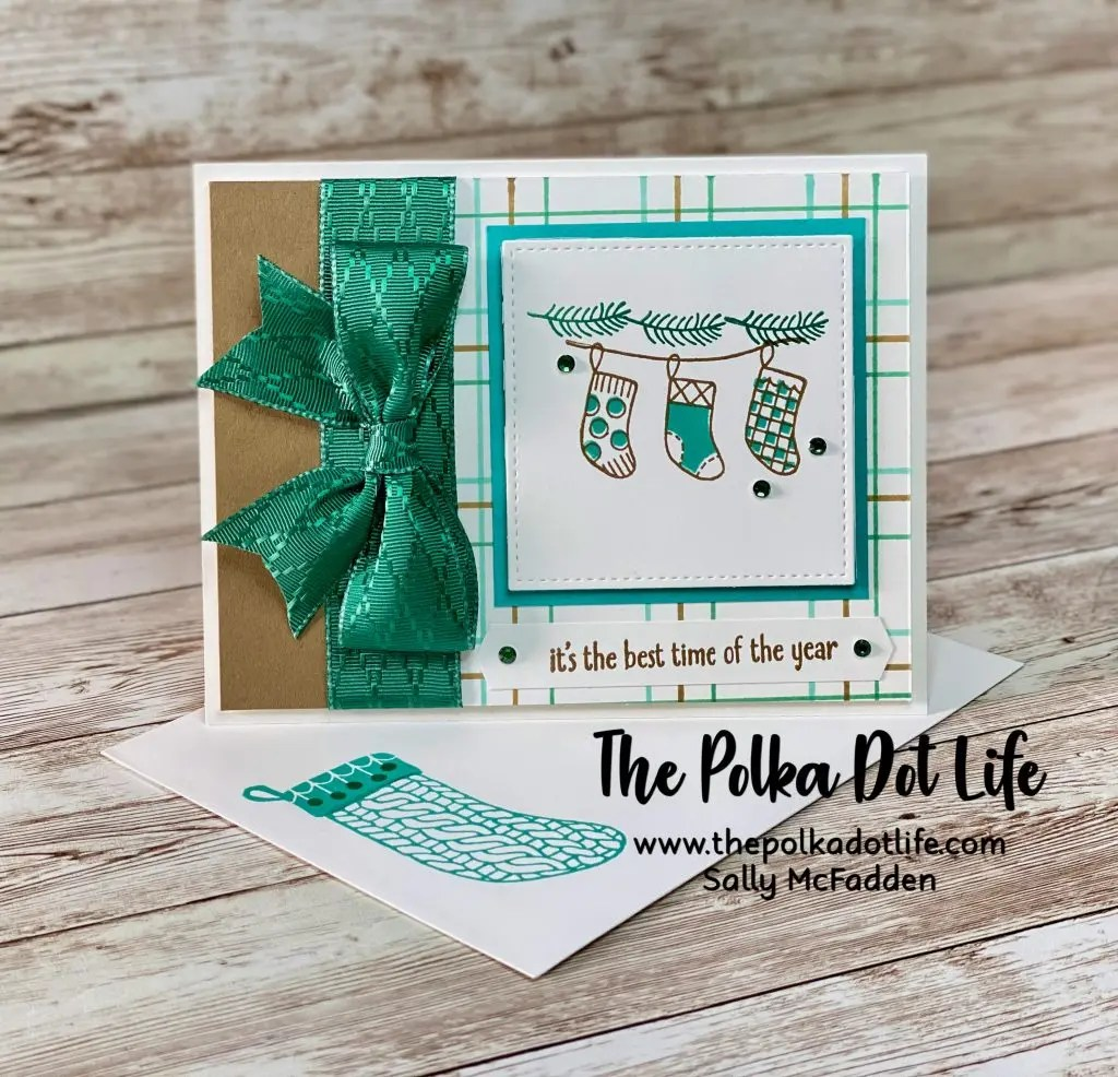 This handmade Christmas card was made using Stampin' Up products.  It has a large ribbon bow in Shaded Spruce and has an image of three stockings on the front.