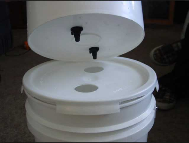 The top bucket sits on the lid of the bottom bucket and the filtered water drains down via gravity.