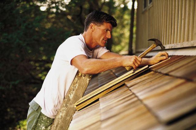man-on-ladder-fixing-shingles
