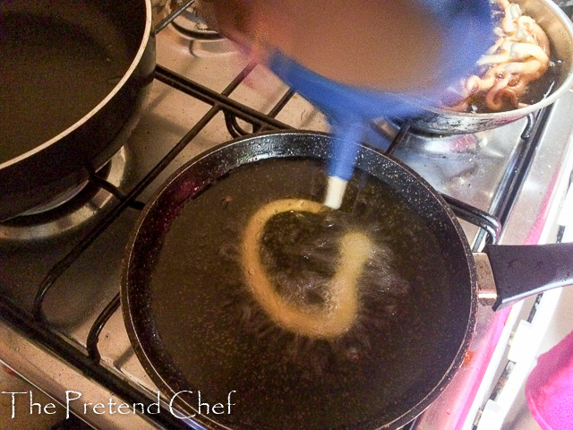 funnel cake batter being poured into hot oil