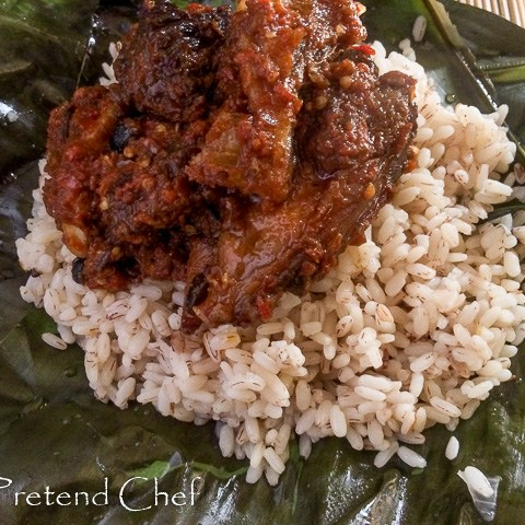 Hot and spicy ofada rice and stew served in fresh banana leaves