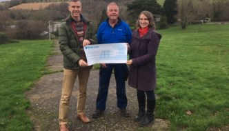 Ernesettle donation picture. A large cheque is being held by three people in a path in a green space. LR Cllr Mark Lowry Volunteer Raymond Morten Cllr Pam Buchan Budshead Woods