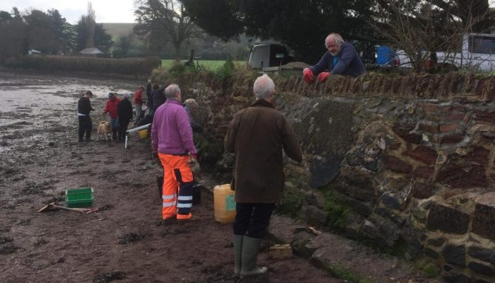 a group of volunteers stood in a muddy estuary as low tide with buckets in the hands protecting the sea wall.