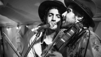 two male singers wearing hats are sharing a microphone