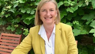 sarah wollaston is wearing a yellow jacket sitting outside drinking a coffee