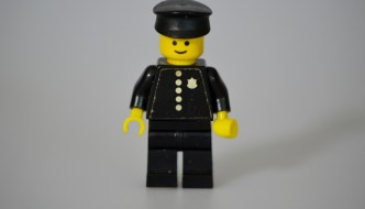 a lego police officer dressed in black with a white background