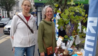 two women are standing next to a plastics free newton abbot stall in the Devon town