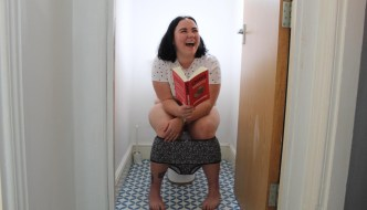 Emily Rooney is sitting on a toilet reading a book laughing with her pants around her legs