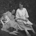 "Two women pose for a photo while reading magazines, including the January 1924 number of ""Breezy Stories."""