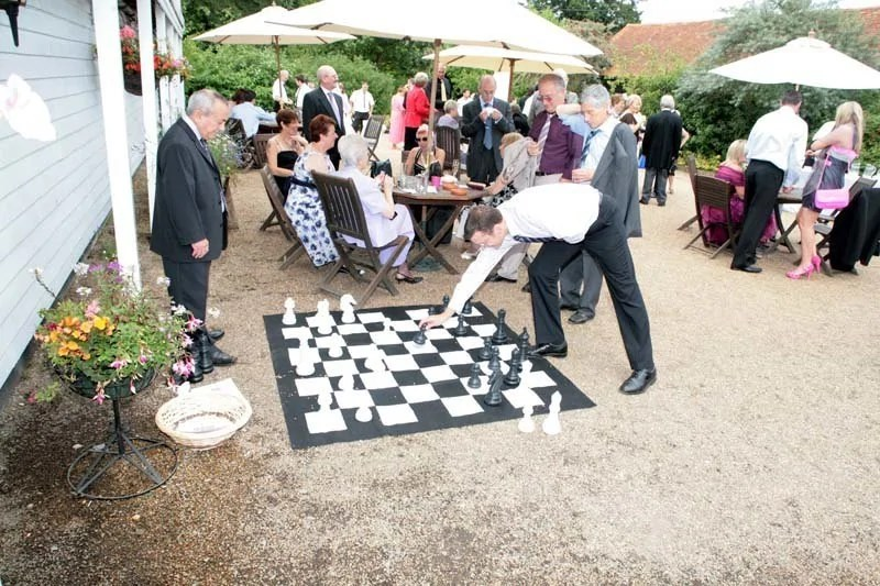 Giant chess being played at a wedding.