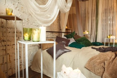 Boho Bedroom Decor Ideas - neutral colours with voile hanging from ceiling, scatter cushions and candles
