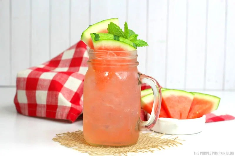 watermelon cocktail in a glass mason jar with handle, with a dish of watermelon wedges in the background.