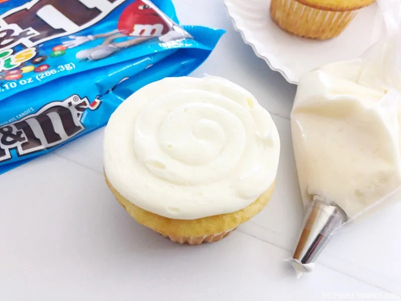 Frosting cupcakes with piping bag.