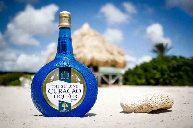 Bottle of Blue Curaçao on a beach
